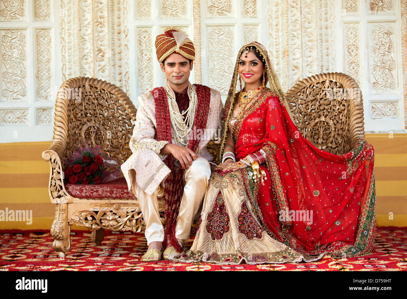 Indian bride and groom in traditional wedding dress sitting on a ...