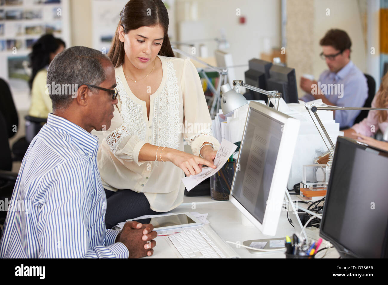 Workers At Desks In Busy Creative Office - Stock Image