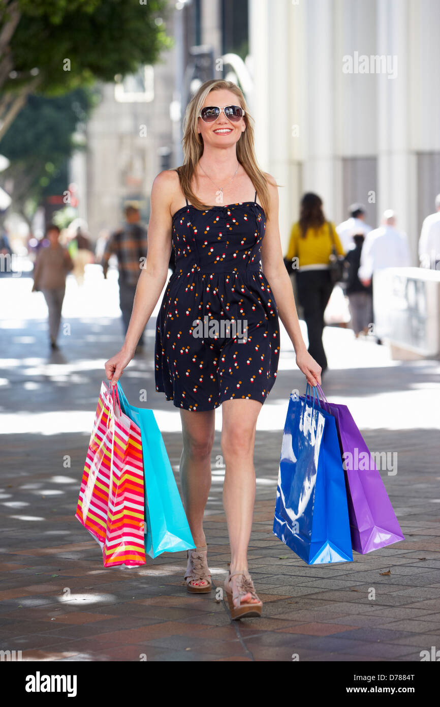 Woman Carrying Shopping Bags On City Street - Stock Image