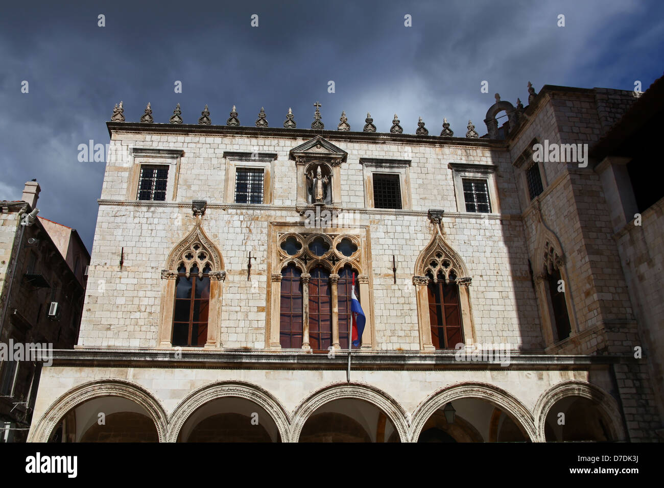 View to the historic Sponza palace in Dubrovnik with dramatic sky in background - Stock Image