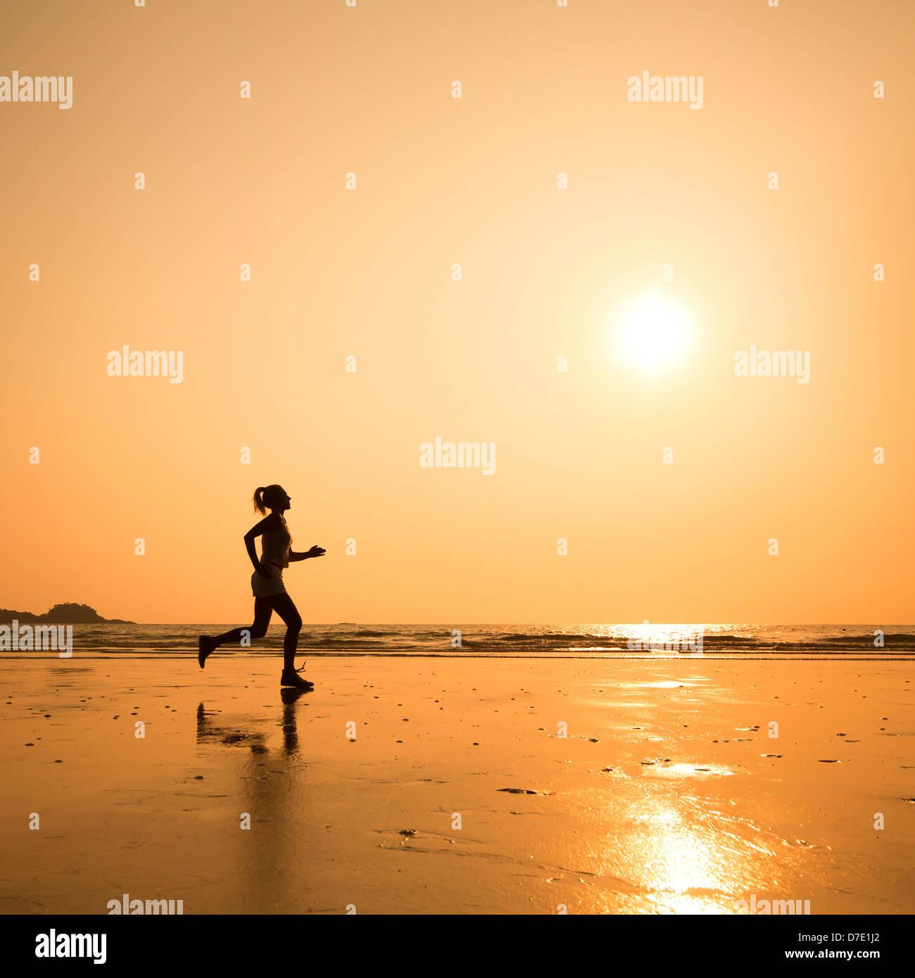 run to purpose, woman silhouette on the beach - Stock Image