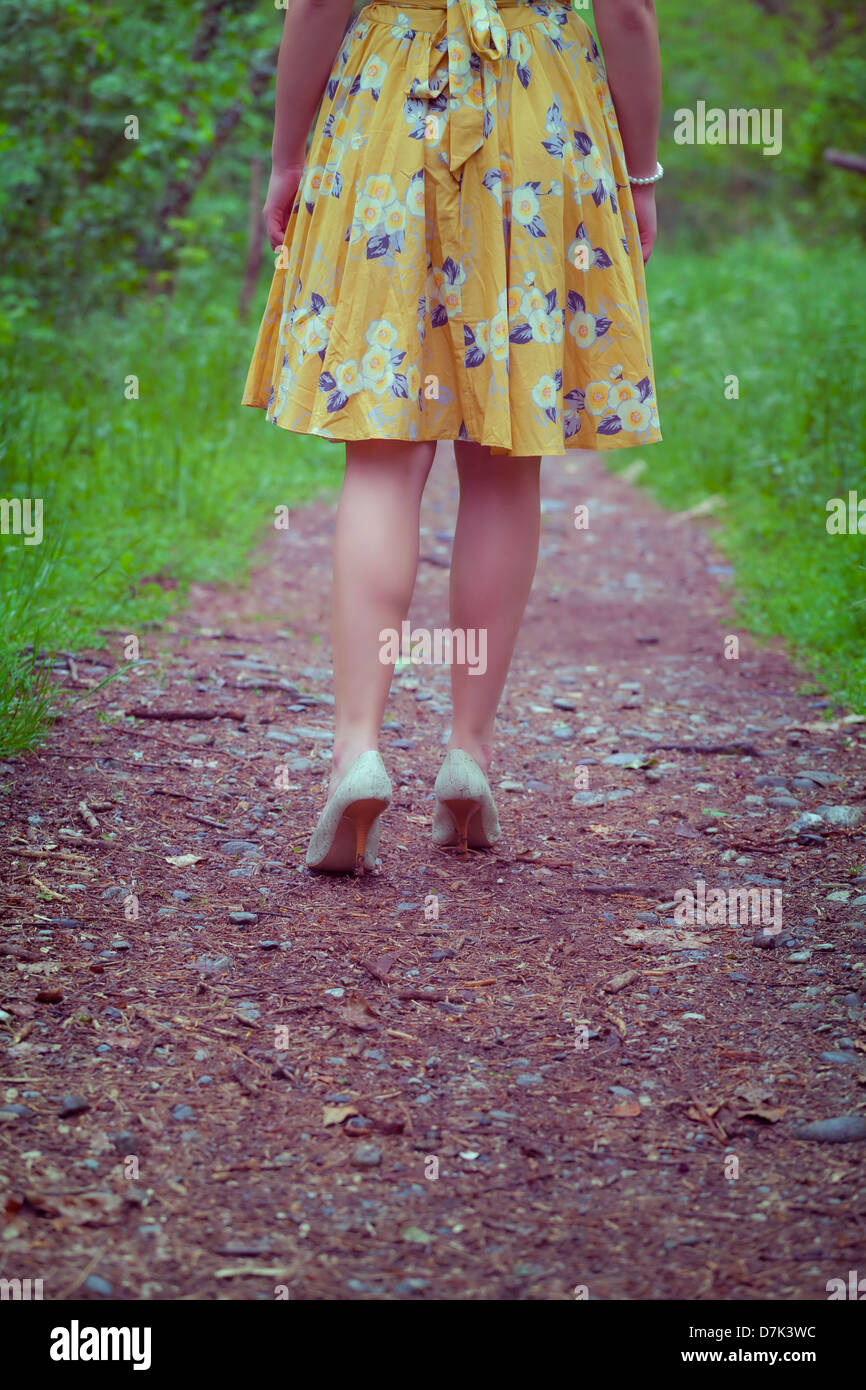 legs of a woman in a yellow dress walking on a path in the woods - Stock Image