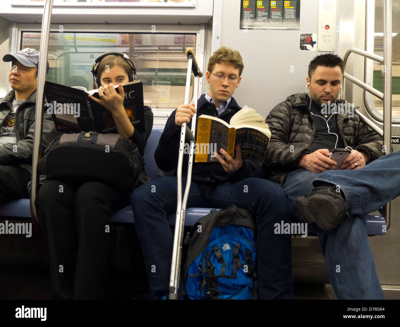 people reading on the subway - Stock Image