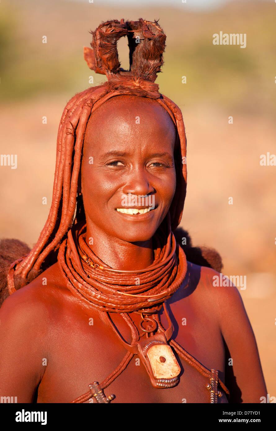 Himba woman inside a mud dwelling hut wearing dress and jewellery and covered in Otjize, Kunene Region, Kaokoland, - Stock Image