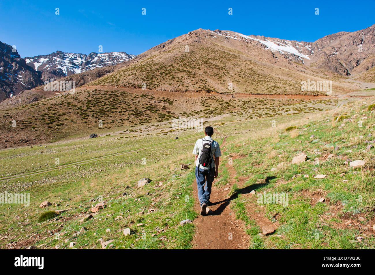 Trekking tour guide walking at Oukaimeden ski resort in summer, High Atlas Mountains, Morocco, North Africa - Stock Image