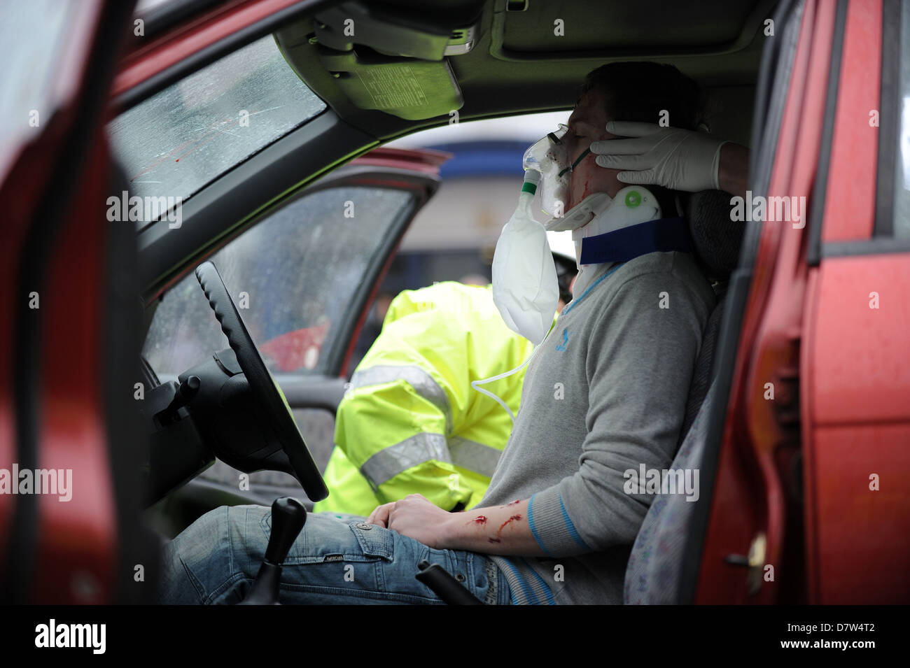 A road traffic accident (rta) victim is dealt with by an ambulance crew after a car crash. - Stock Image