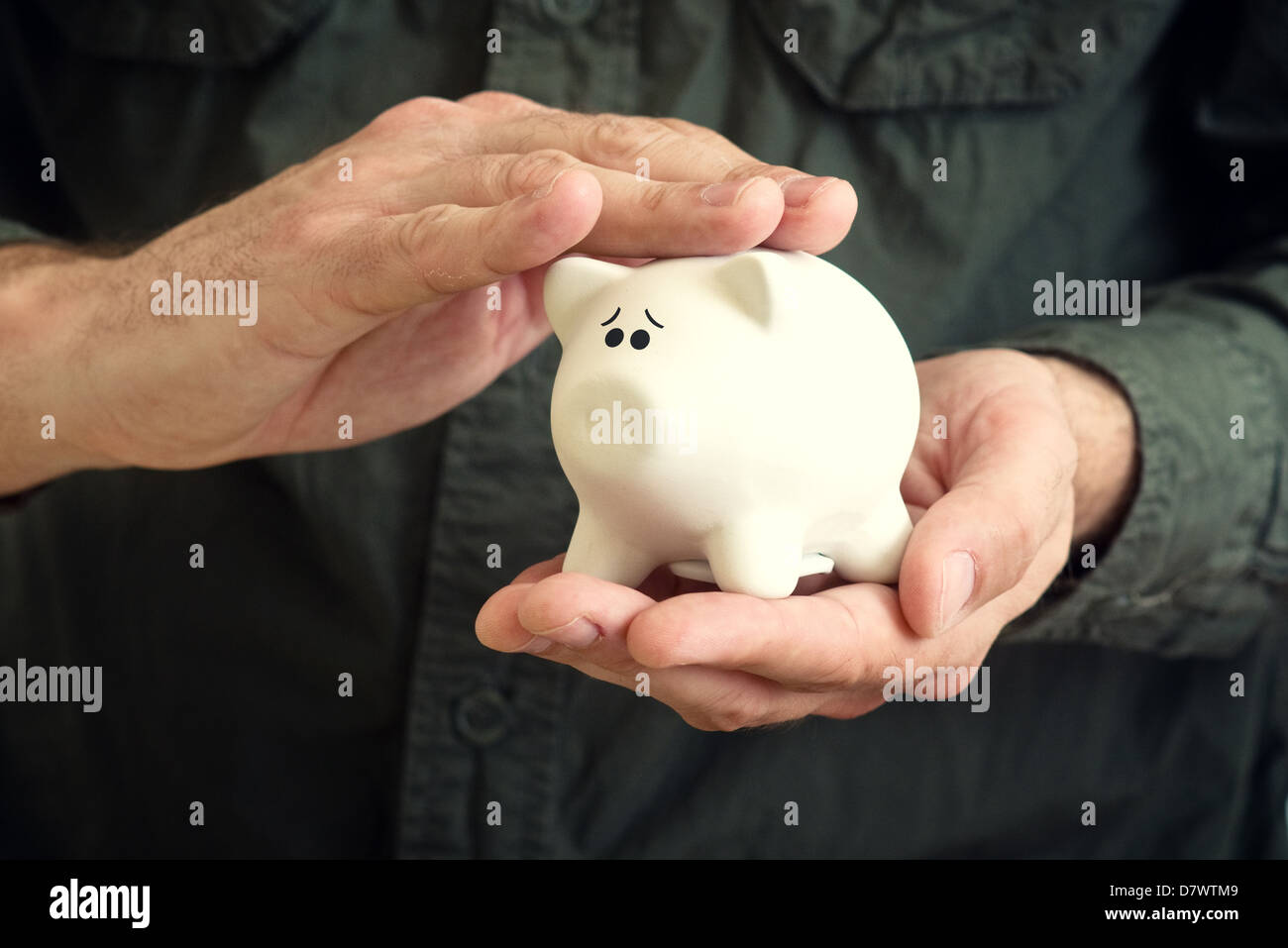Hand cuddles white piggy coin bank with scared look in its eyes. - Stock Image