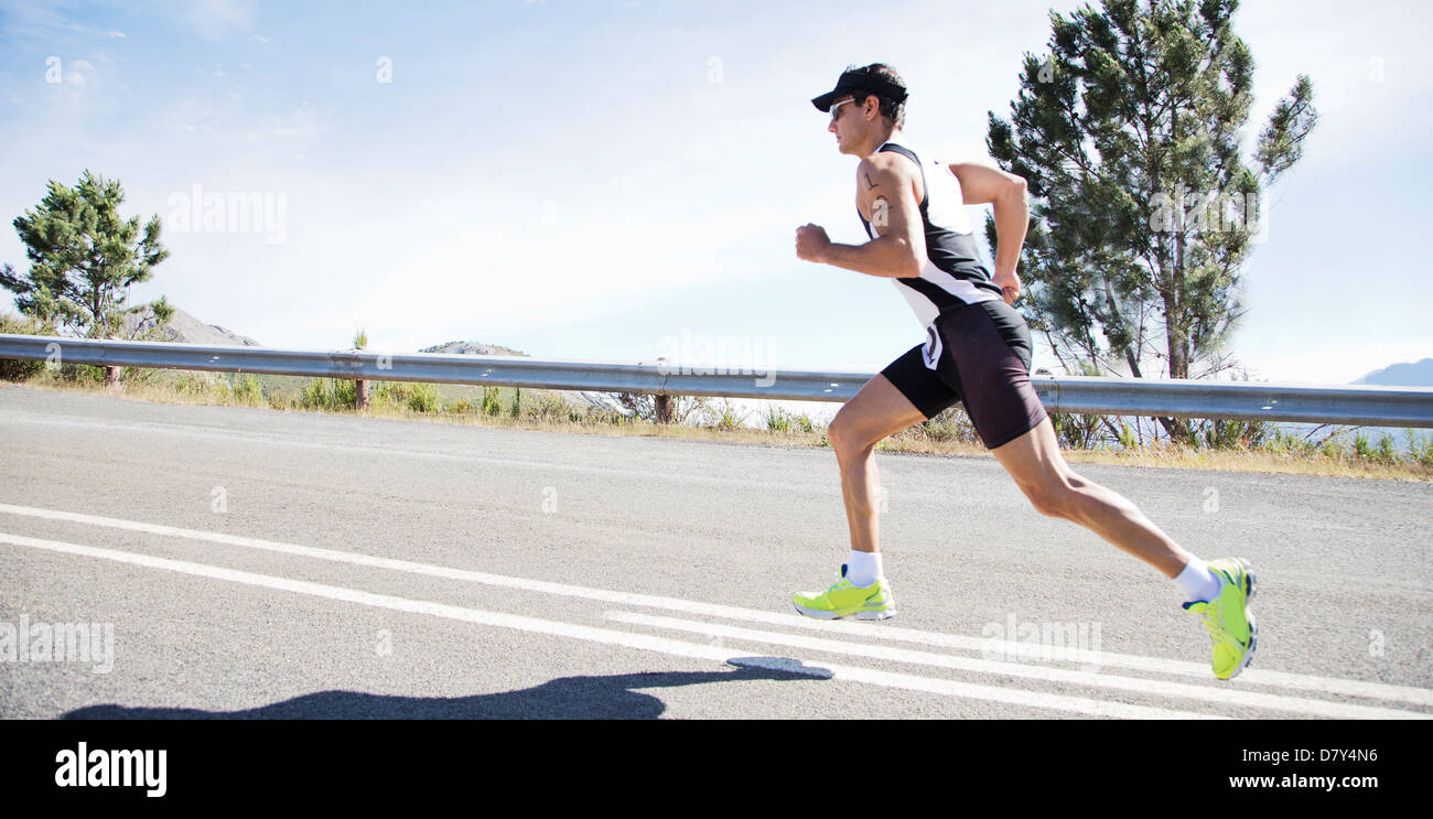 Runner in race on rural road - Stock Image
