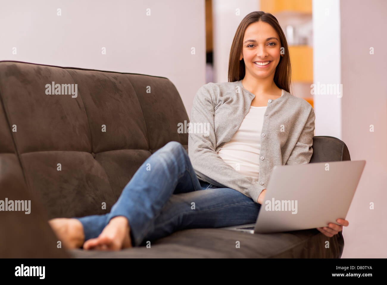 Smiling female teleworking at home - Stock Image