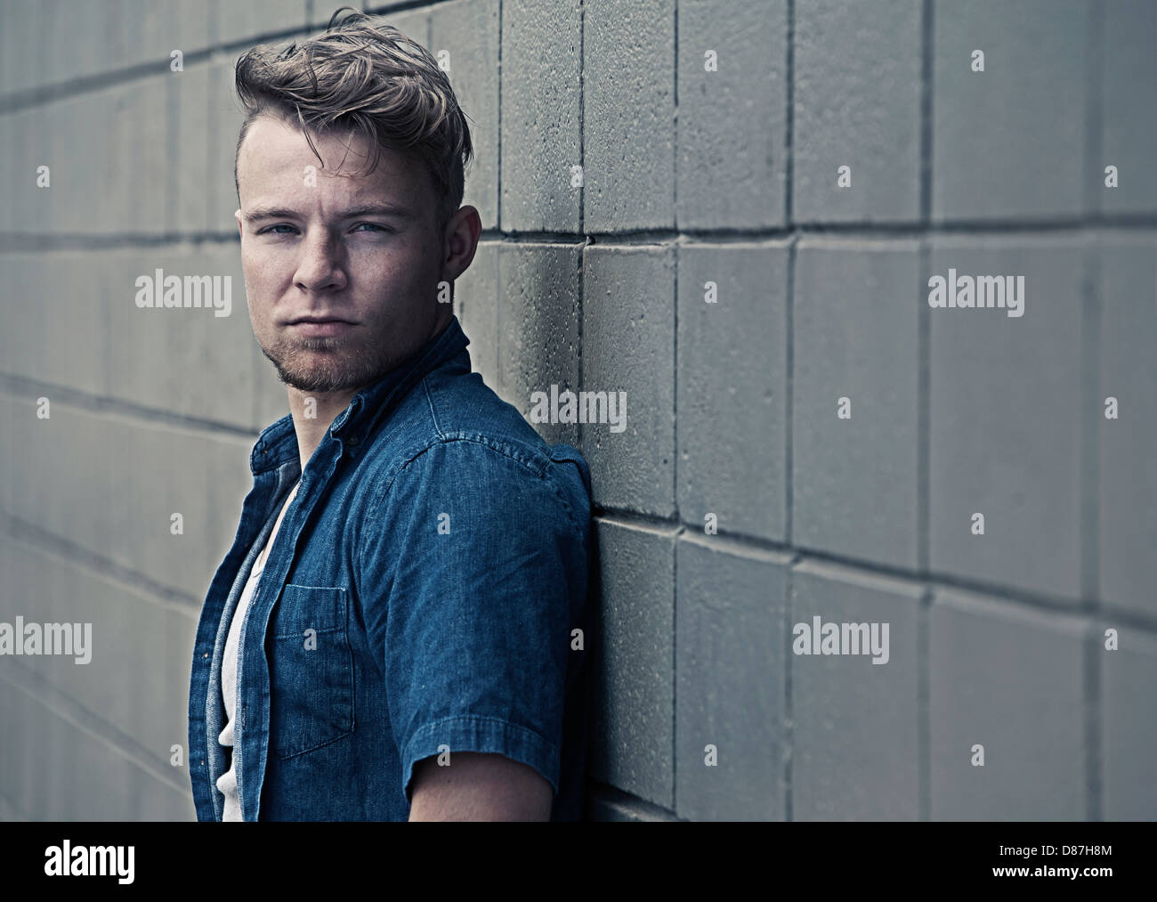 Man standing against block wall - Stock Image