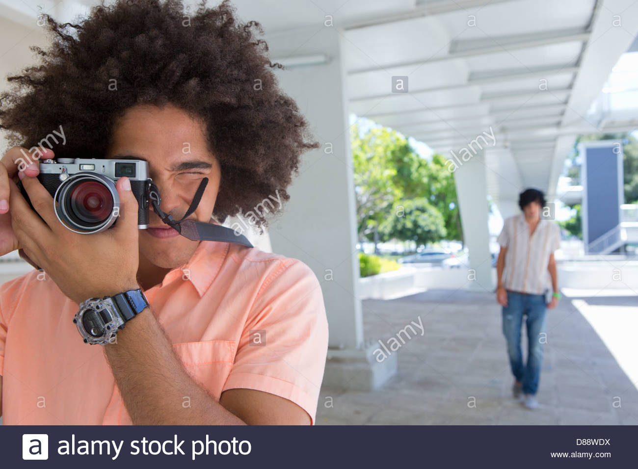 Portrait of young man using camera - Stock Image
