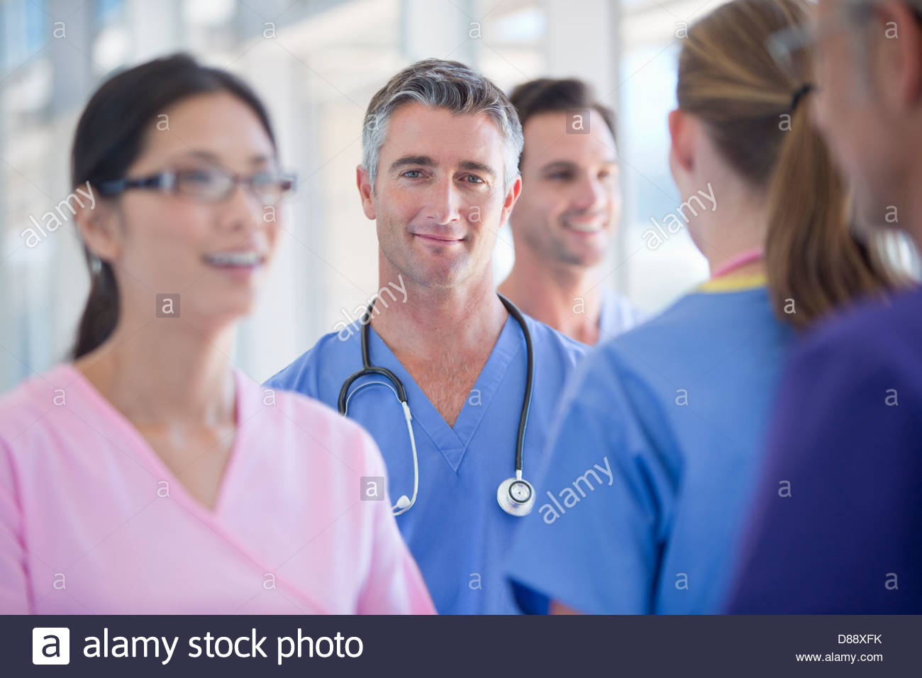 Portrait of smiling doctor among co-workers - Stock Image