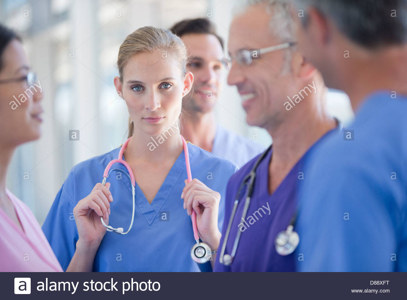 Portrait of serious doctor among co-workers - Stock Image
