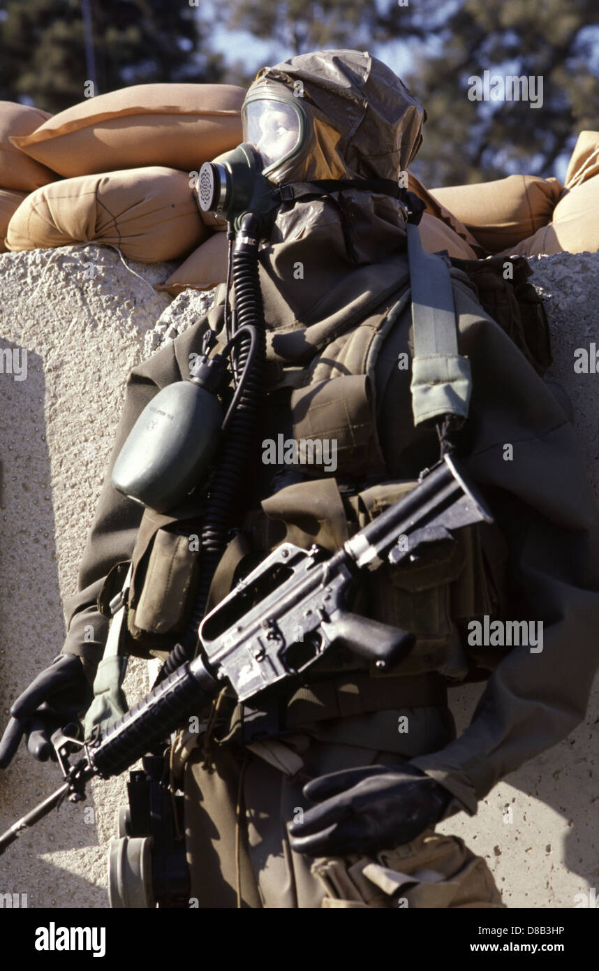 An armed manikin dressed in soldier outfit with gas mask and M-16 rifle - Stock Image