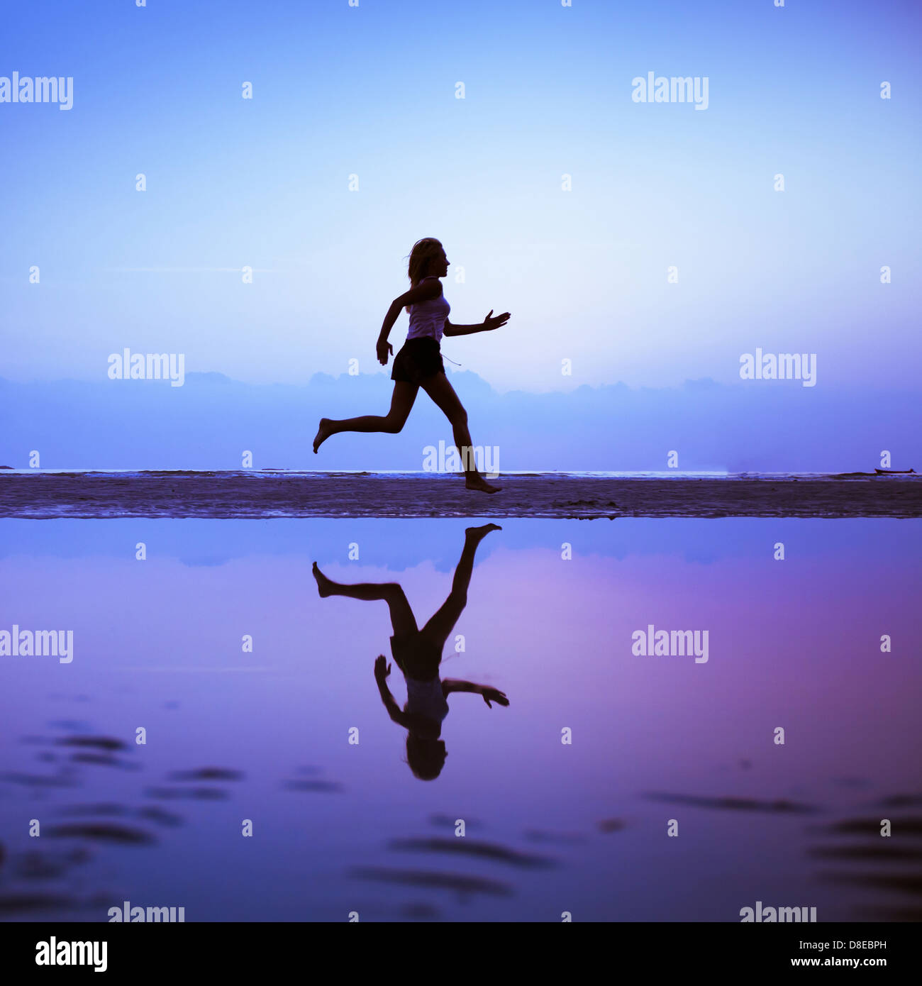 Female runner silhouette is mirrored below with a blue sunset sky as background - Stock Image