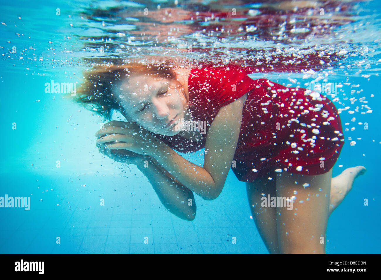 imagination, underwater portrait of woman in red dress - Stock Image