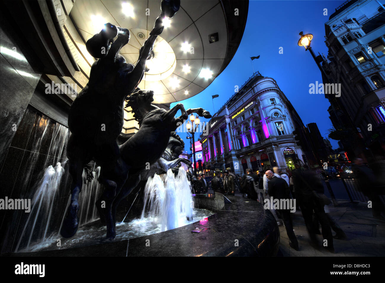 Piccadilly,Circus,London,at,dusk,statue,art,works,of,pieces,1992,people,walking,nearby,on,the,pavement,street,road,water,feature,fountain,fountains,Soho,brilliant,horse,Trafalgar,Square,spotlight,spot,light,rushing,crowd,night,shot,nightshot,wide,central,capital,city,tourist,tourism,travel,gotonysmith,Buy Pictures of,Buy Images Of