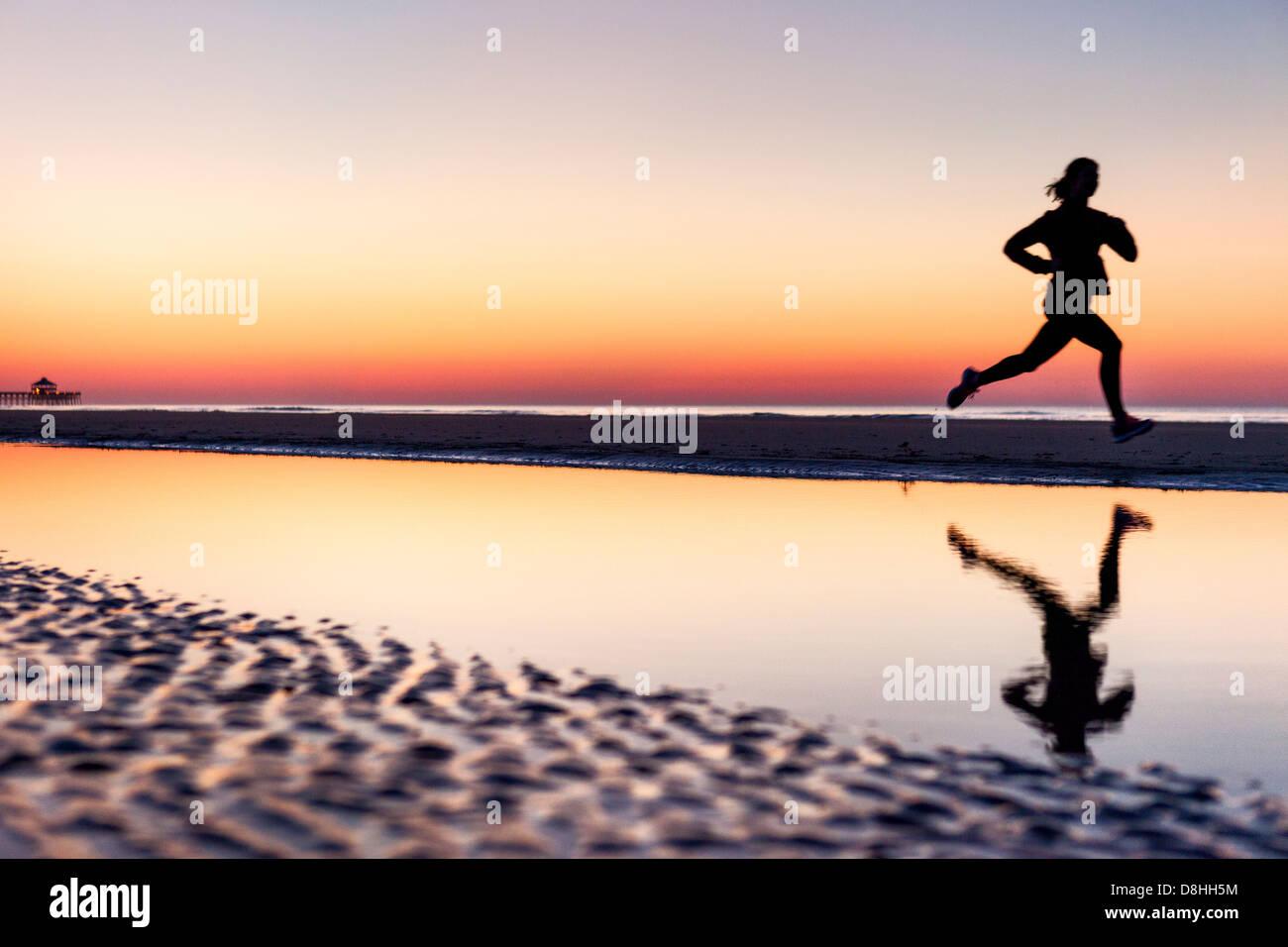 Female jogger at beach - Stock Image