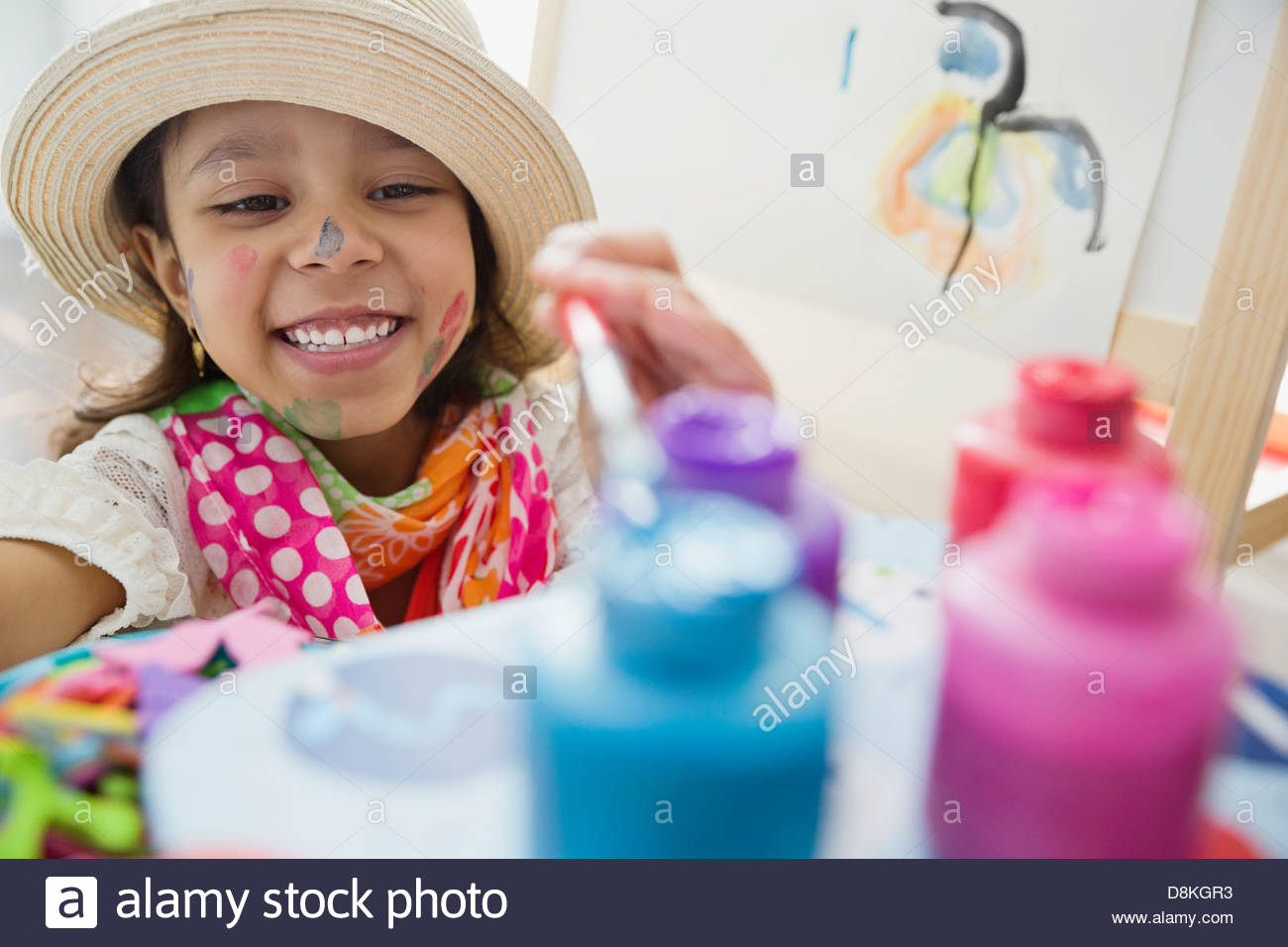 Young artist reaching for paints - Stock Image
