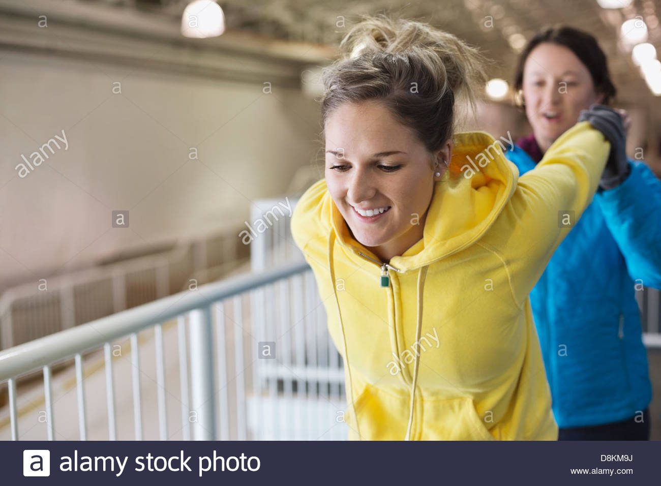 Female athlete stretching with coach - Stock Image