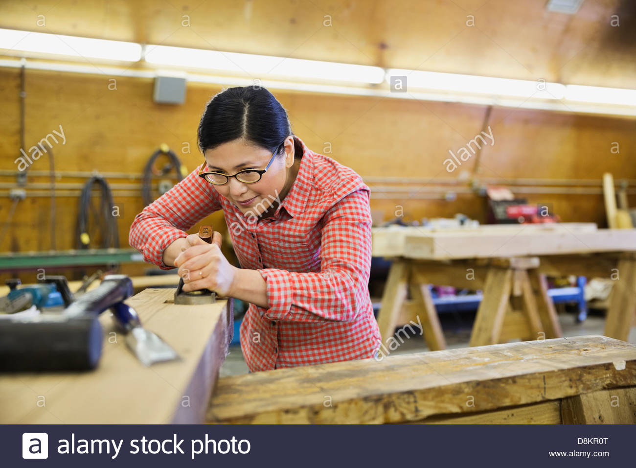 Woodworker using hand plane on wooden beam - Stock Image
