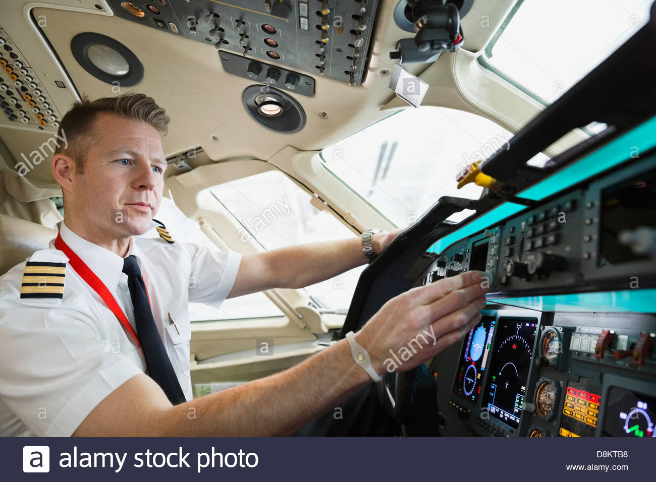 Male pilot checking control panel in airplane cockpit - Stock Image