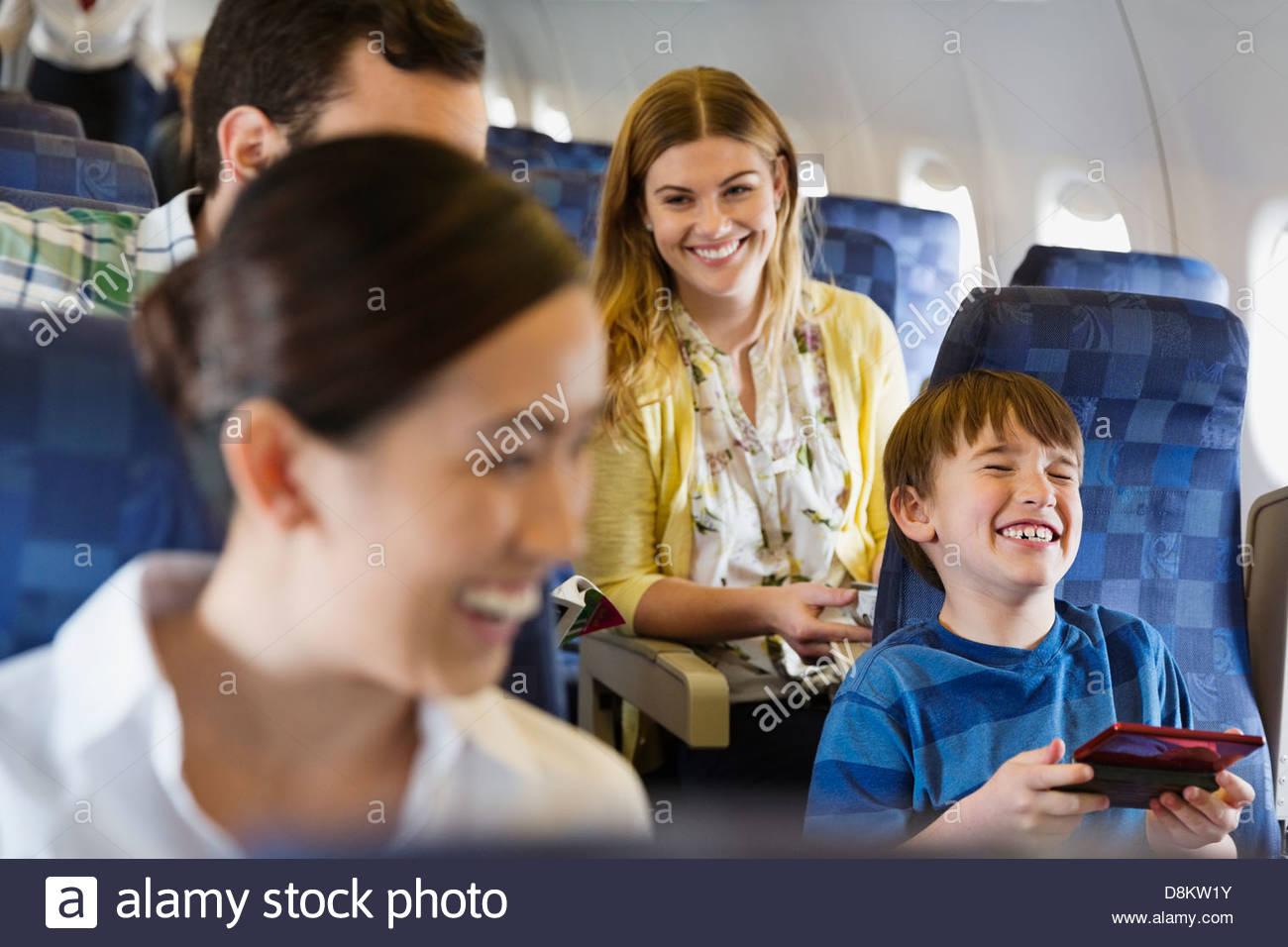 Cheerful passengers traveling in airplane - Stock Image