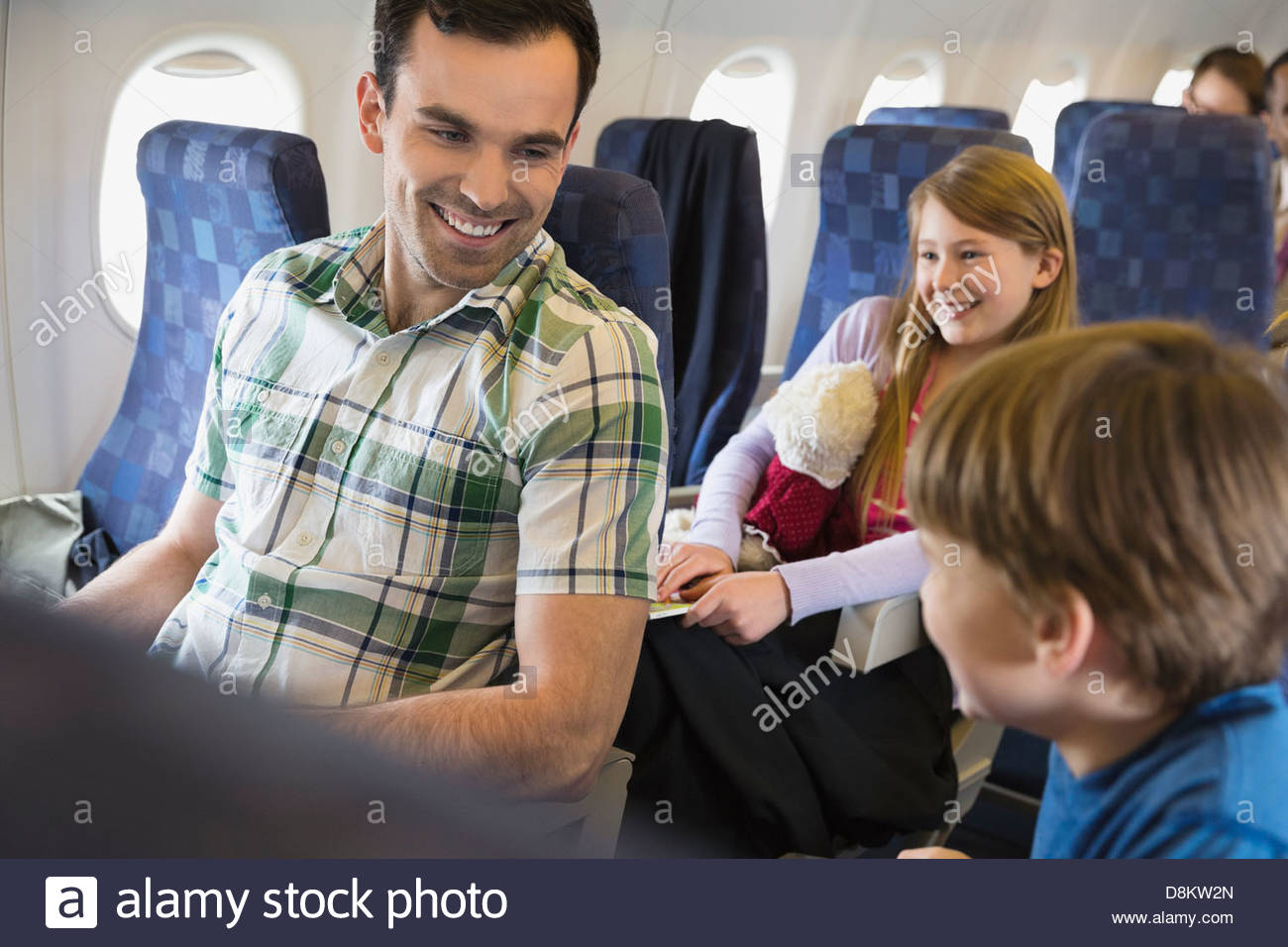 Father with children traveling in airplane - Stock Image