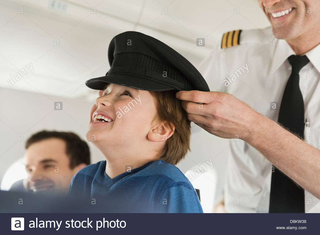 Male pilot placing his cap on boy's head in airplane - Stock Image