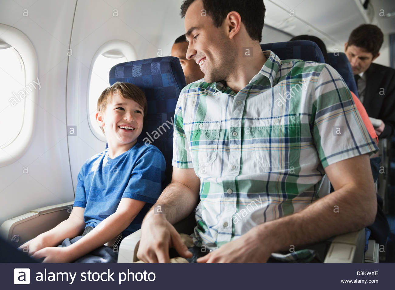 Smiling father and son traveling in airplane - Stock Image