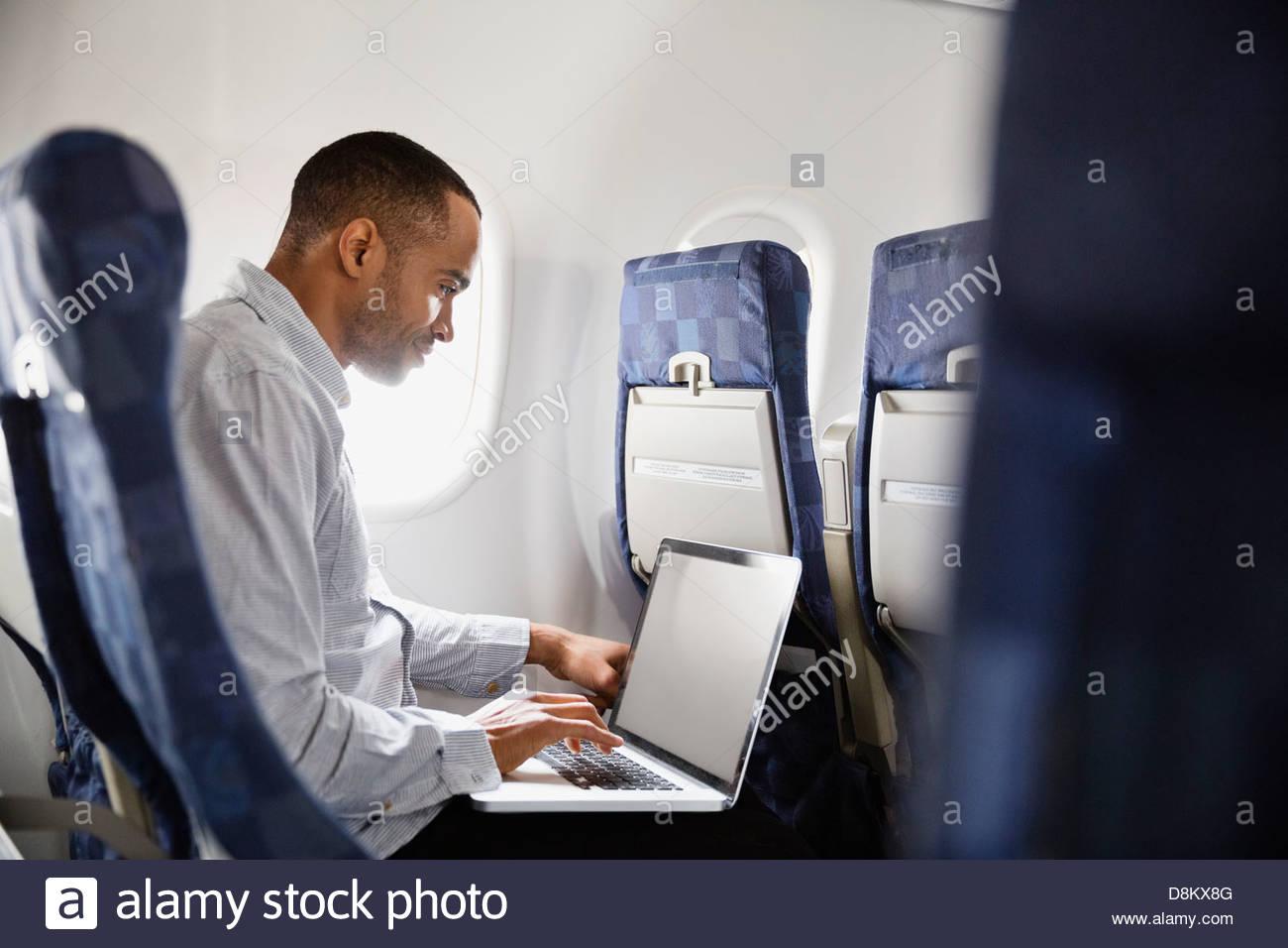 Man using laptop in airplane - Stock Image