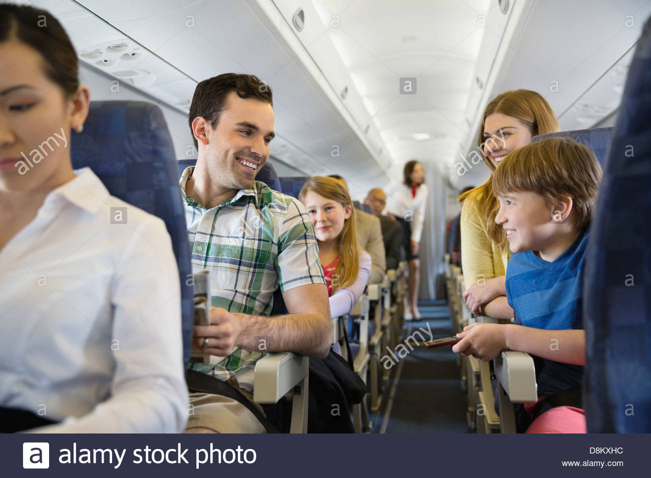 Smiling family traveling in airplane - Stock Image