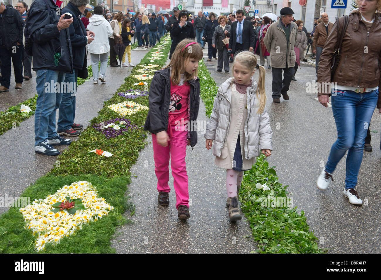 People walking on street decorated with wild flowers Easter Sunday Flower Torches Festival São Brás de - Stock Image