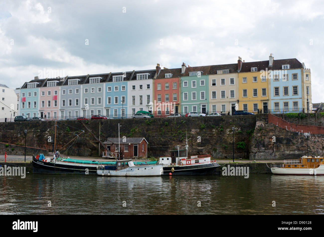 A terrace of colourful houses in Redcliffe Parade seen across the Floating Harbour in Bristol. - Stock Image