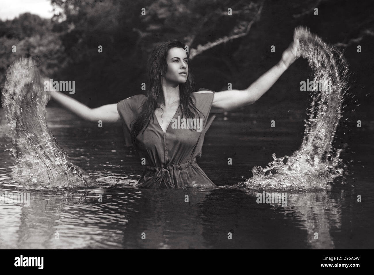Woman splashing water out of river - Stock Image