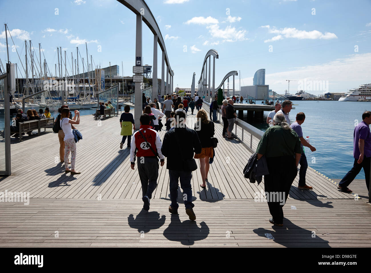 people walking along rambla de mar walkway in the old port of stock