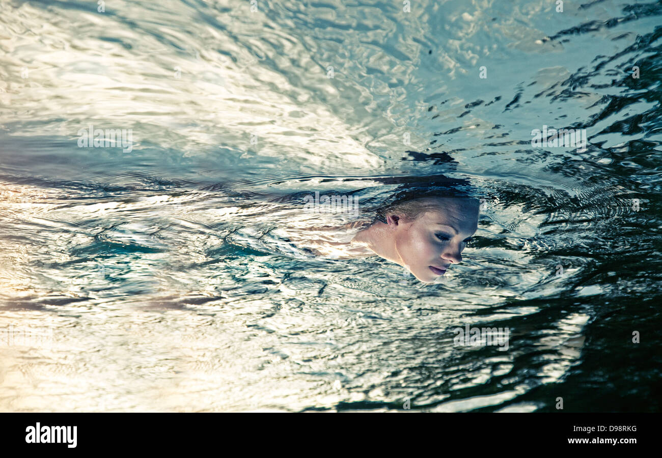 Woman floating in water - Stock Image
