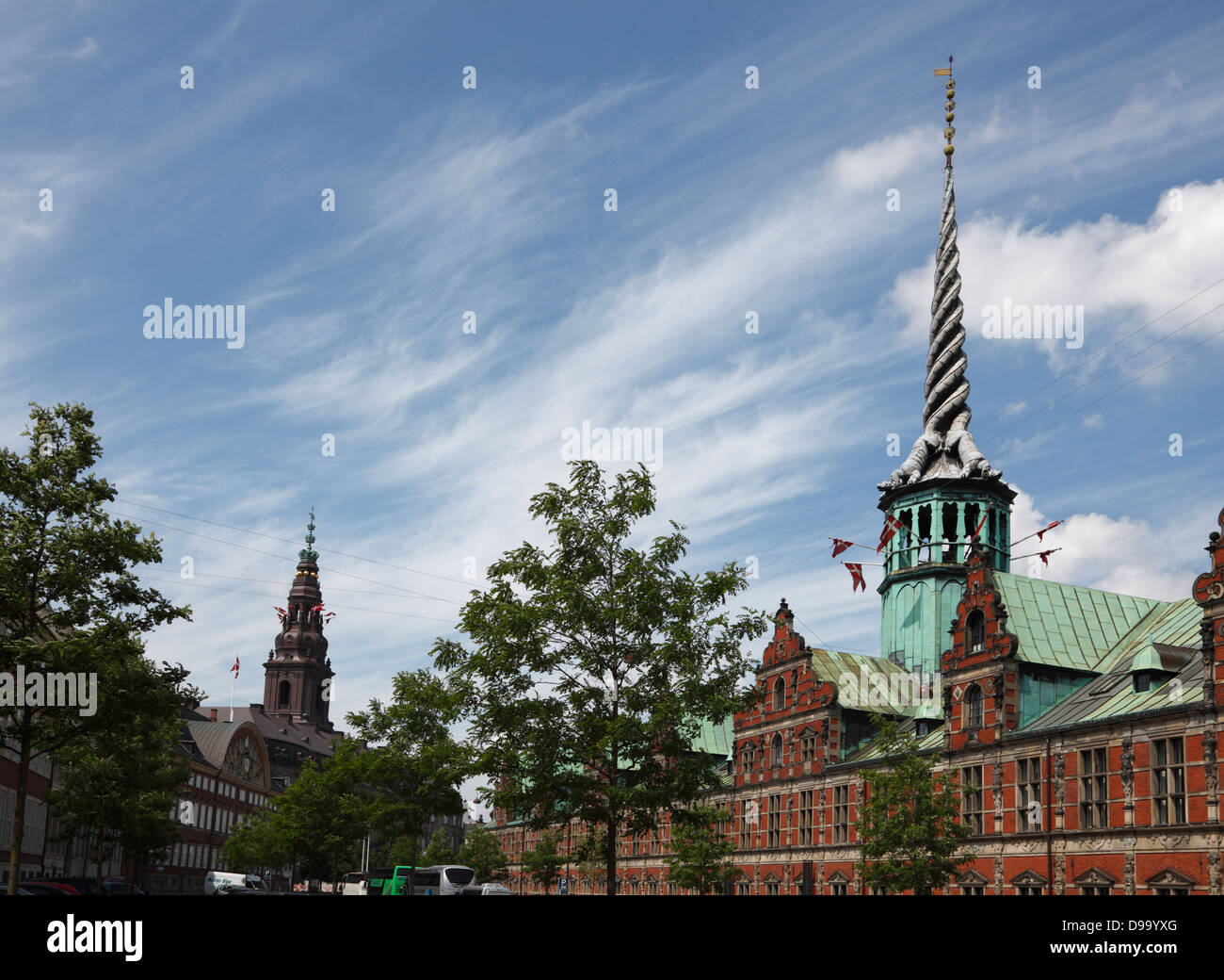 The old stock exchange and the Christiansborg Palace in the background, both flying the Danish flag from the turret - Stock Image