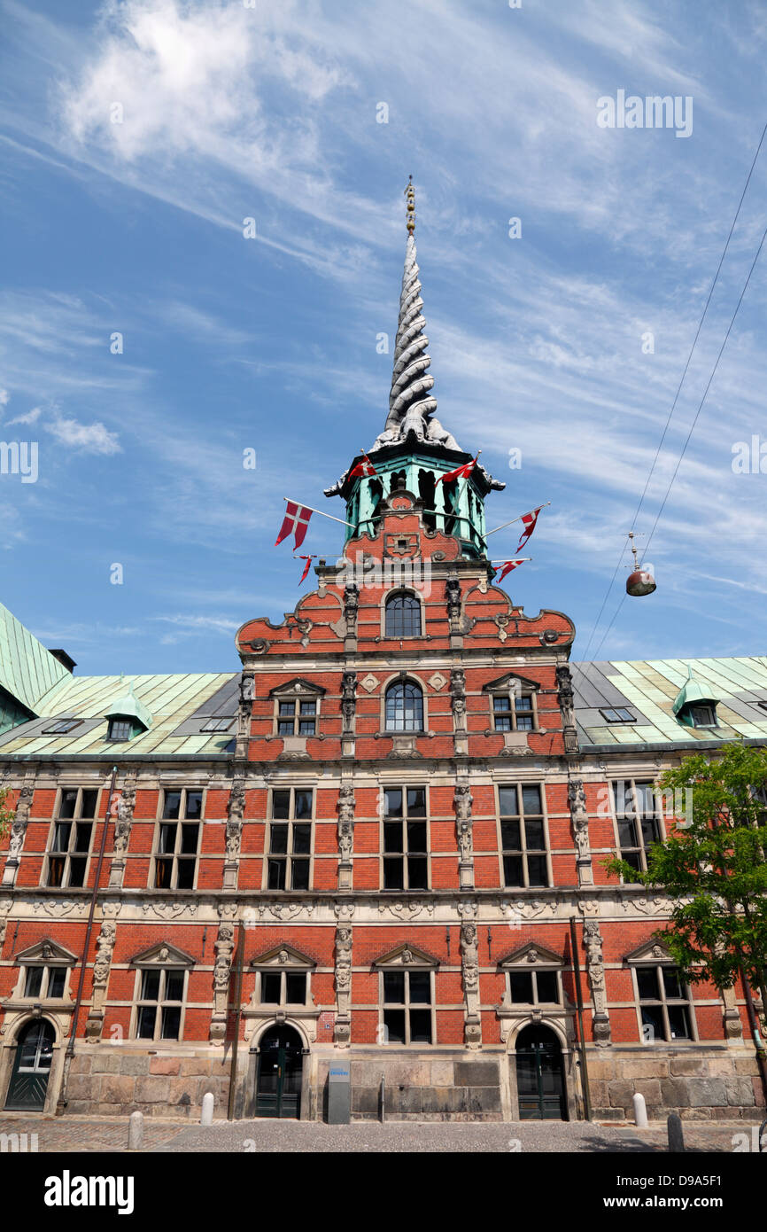 The old stock exchange, Børsen, flying the Danish flag from the turret openings to celebrate Valdemarsdag and - Stock Image