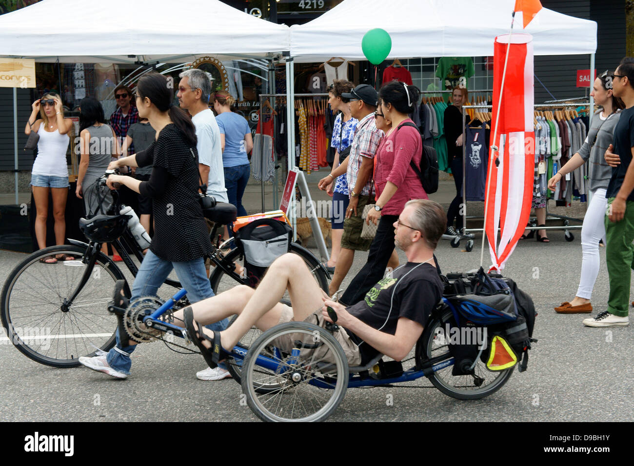 Man riding a reclining bicycle at the Car Free Day festival on Main Street in Vancouver, British Columbia Stock Photo