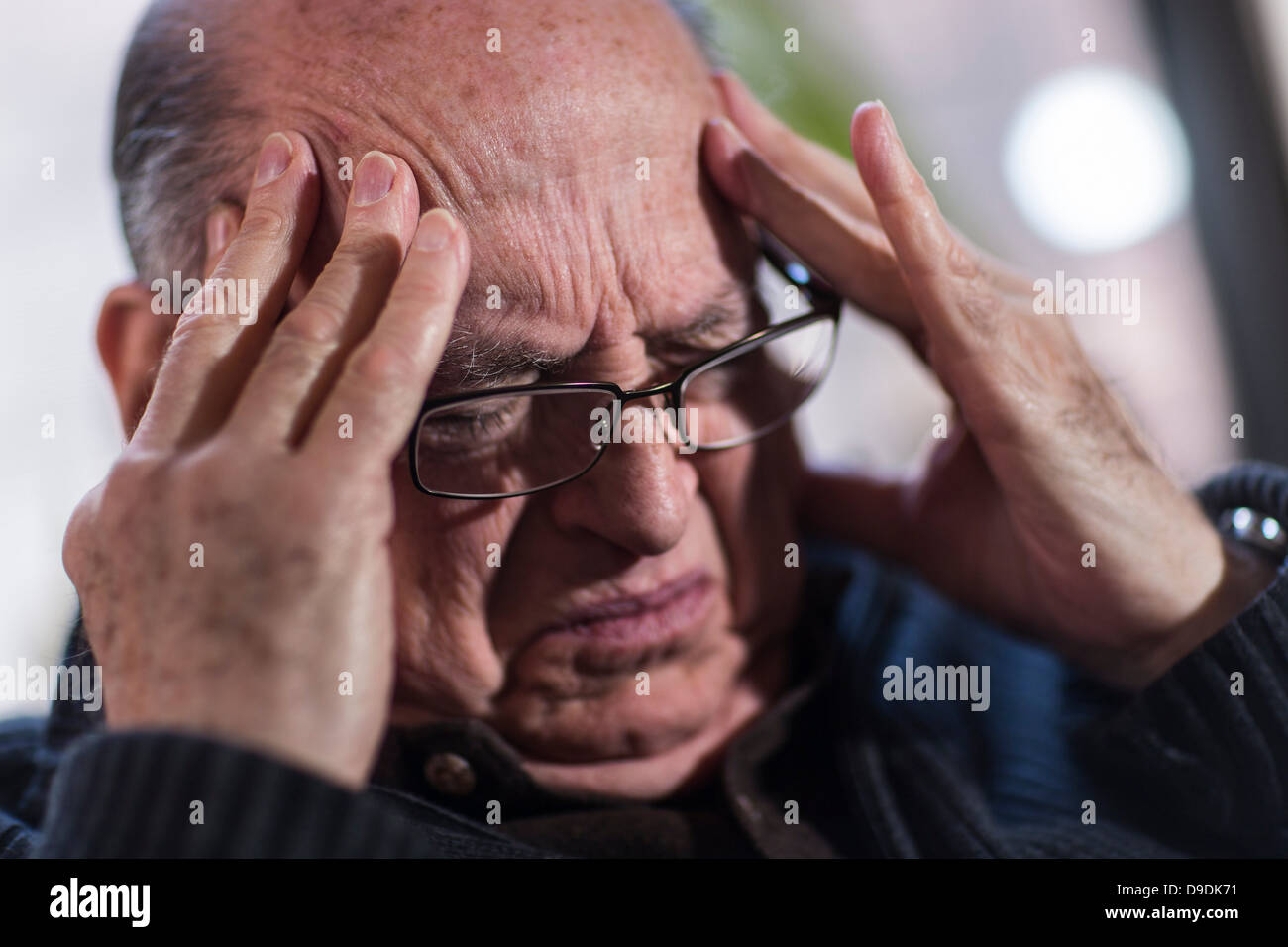 Senior man with eyes closed, wearing glasses, looking stressed Stock Photo