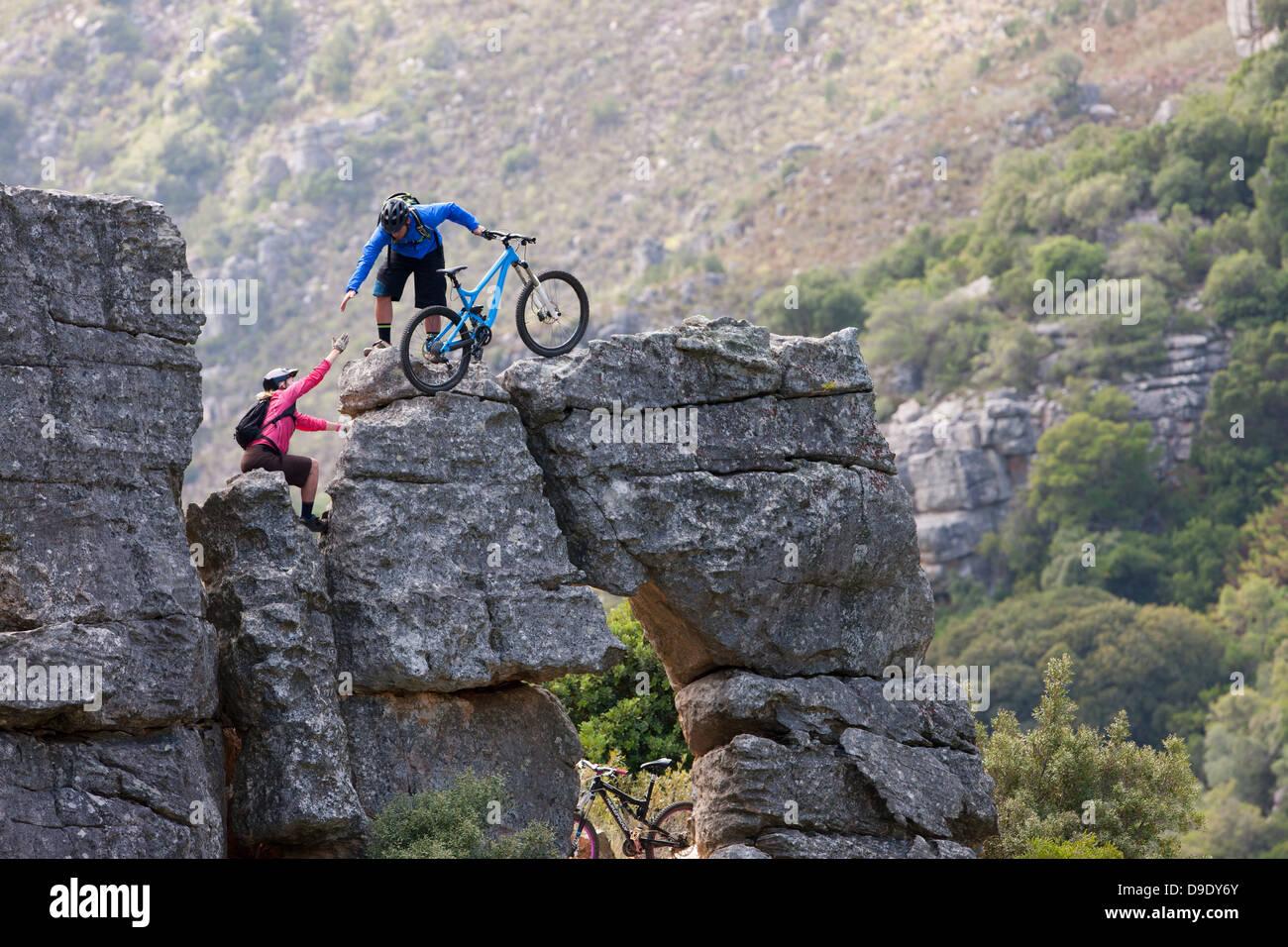 Mountain biking couple climbing rock formation - Stock Image