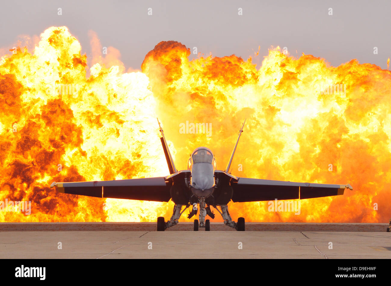 An F/A-18 Hornet sits on the flight line as a wall of fire detonates behind it. - Stock Image