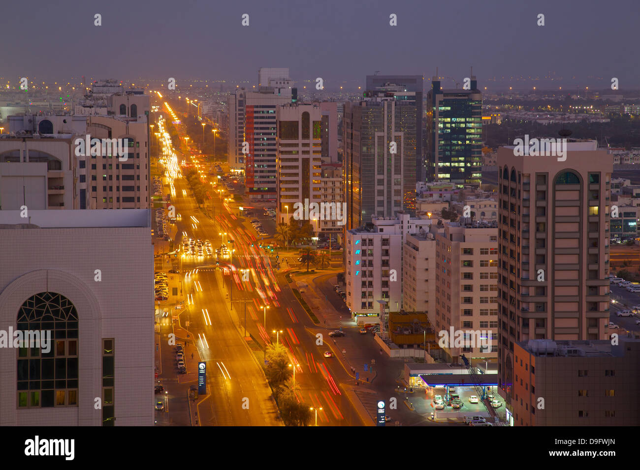 City skyline and Rashid Bin Saeed Al Maktoum Street at dusk, Abu Dhabi, United Arab Emirates, Middle East - Stock Image