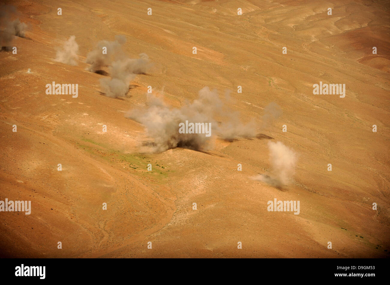 Dust rises from the impact points of KP long-guided rockets. - Stock Image