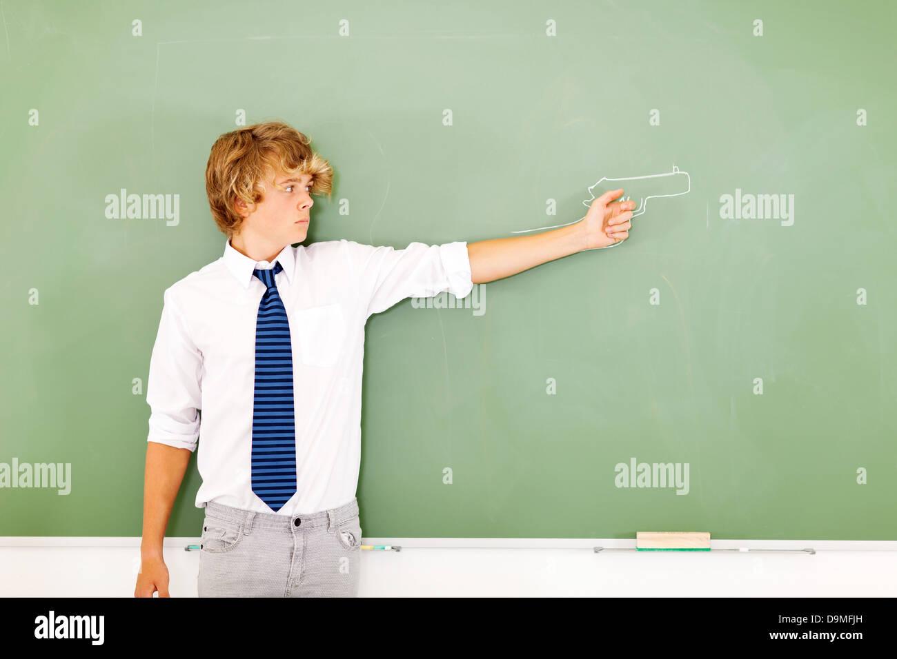 violent high school boy holding a gun drawn on chalkboard - Stock Image
