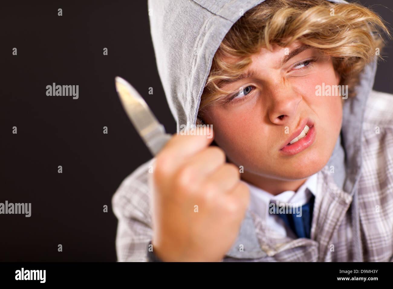 violent teen boy holding a knife on black background - Stock Image