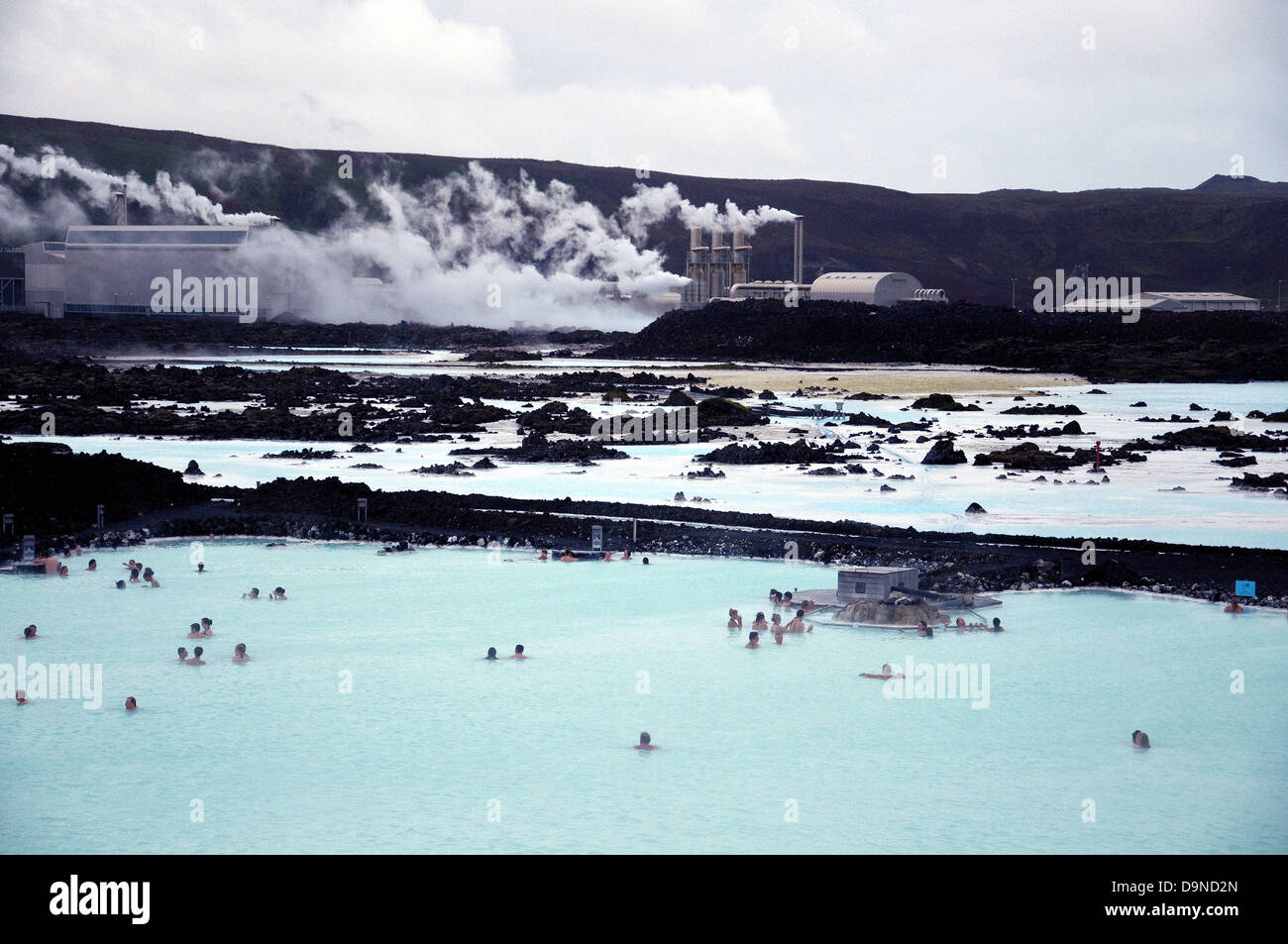 Iceland's famous Blue Lagoon, popular swimming lake in the foreground, the Svartsengi geothermal energy plant - Stock Image