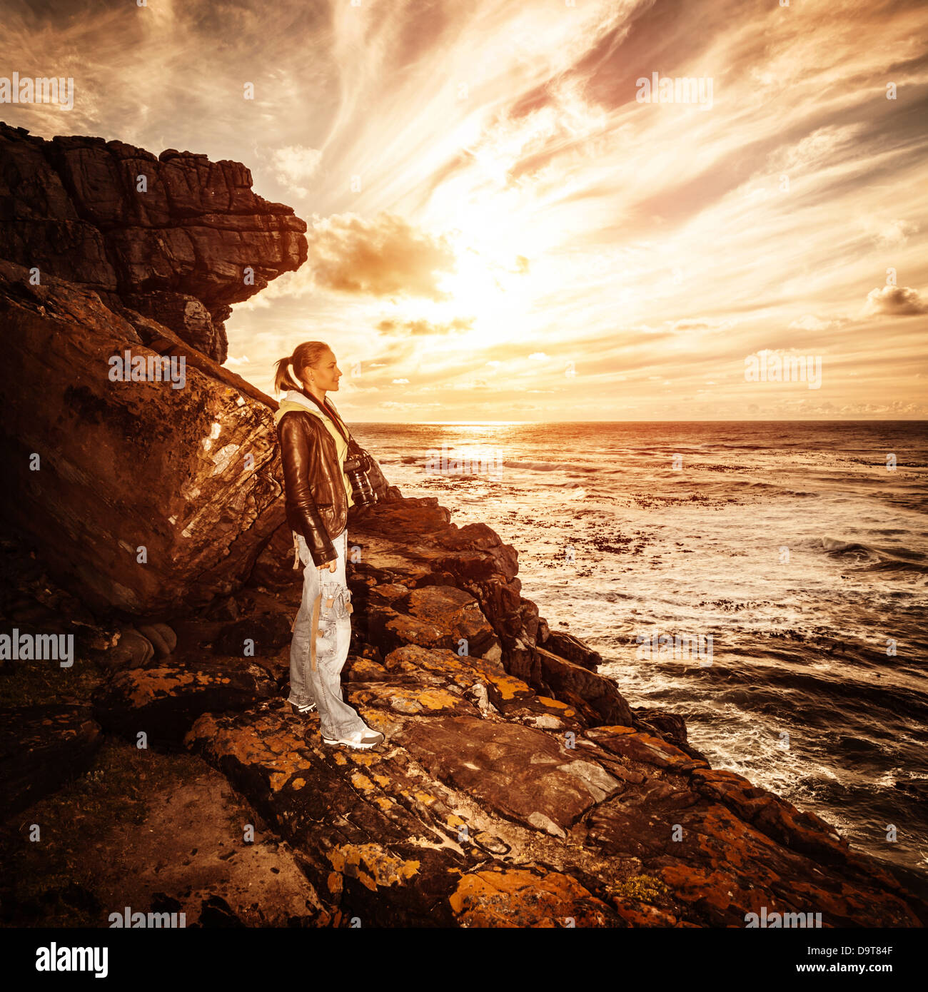 Beautiful photographer woman standing on rocky seashore and enjoying sunset, adventure journey in South Africa, - Stock Image