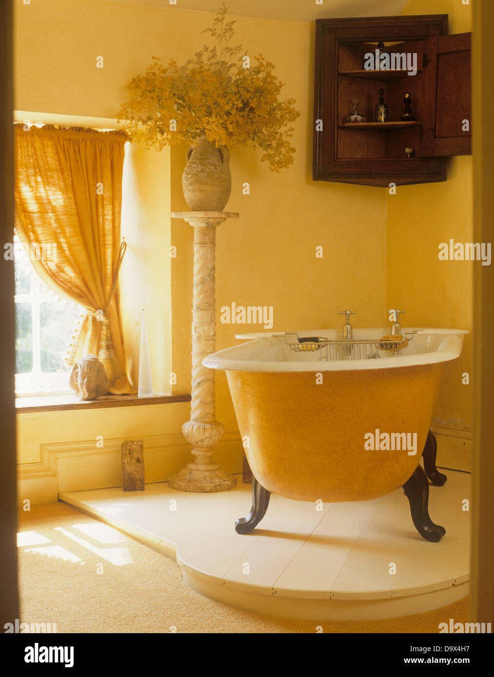 Claw foot bath on raised floor in yellow bathroom with antique ...